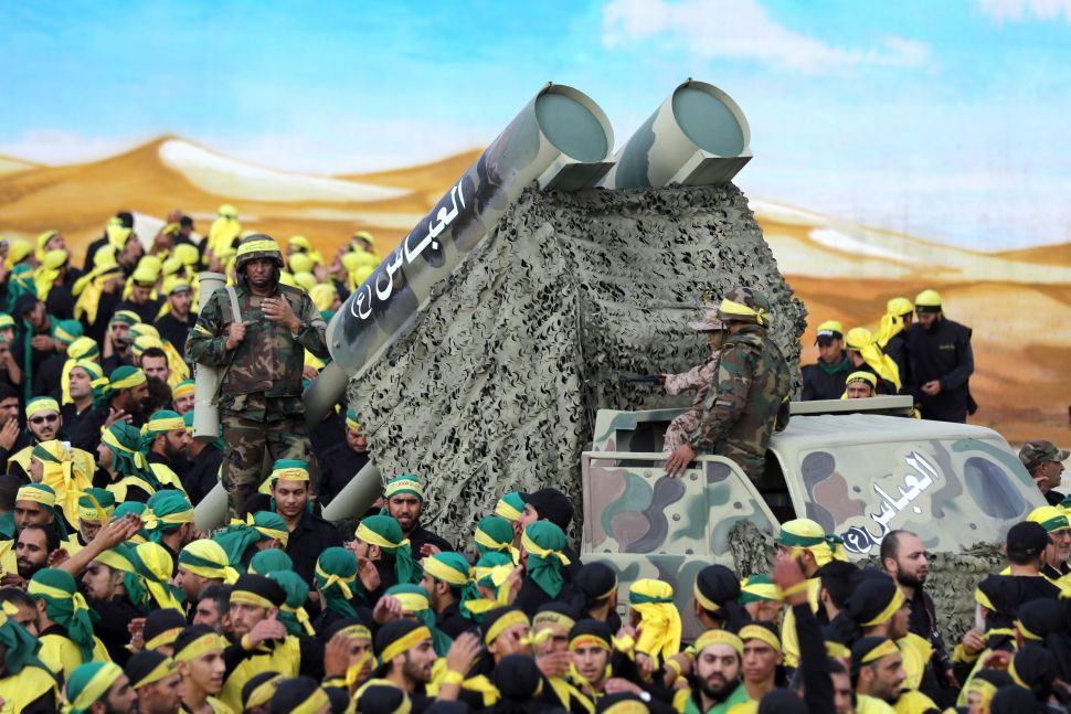 Members of Lebanon's powerful Shiite movement Hezbollah parade with a mock missile launcher .
