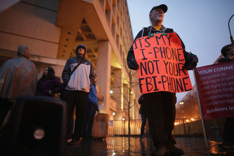"WASHINGTON, DC - FEBRUARY 23: Organized by Fight for the Future, about a dozen protestors demonstrate outside the Federal Bureau of Investigation's J. Edgar Hoover headquarters in support of Apple and against a move by the federal government to force the computer company to create a ""backdoor"" to the iPhone February 23, 2016 in Washington, DC. Last week a federal judge ordered Apple to write software that would allow law enforcement agencies investigating the December 2, 2015 terrorist attack in San Bernardino, California, to hack into one of the attacker's iPhone. Apple is fighting the order, saying it would create a way for hackers, foreign governments, and other nefarious groups to invade its customers' privacy. (Photo by Chip Somodevilla/Getty Images)"