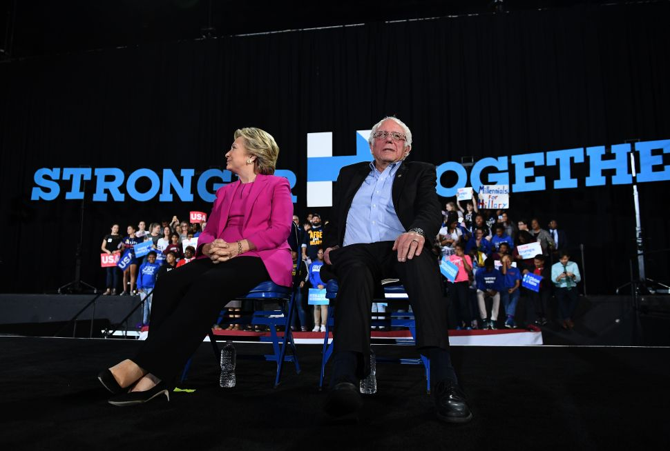 Hillary Clinton and Bernie Sanders listen to singer Pharrell Williams during a campaign rally in Raleigh, North Carolina, on November 3, 2016.