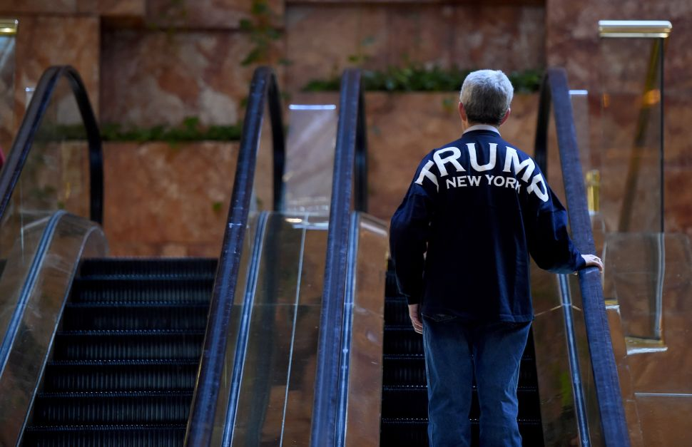 A Trump supporter takes the escalator to the 2nd level at Trump Tower as President-elect Donald Trump holds meetings in his office at Trump Tower on 5th Avenue November 11, 2016. / AFP / TIMOTHY A. CLARY