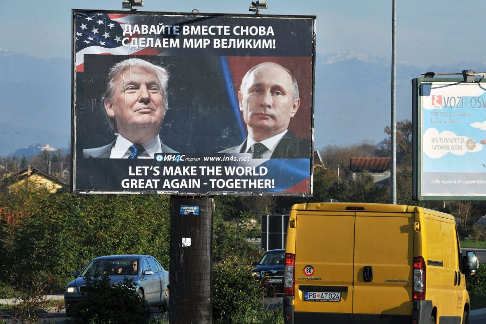 Cars pass by a billboard showing US President-elect Donald Trump and Russian President Vladimir Putin placed by pro-Serbian movement in the town of Danilovgrad on November 16, 2016. Russian President Vladimir Putin and Donald Trump spoke on the phone on November 15, evening and agreed on the need to normalise ties between Washington and Moscow, the Kremlin said. / AFP / Savo PRELEVIC