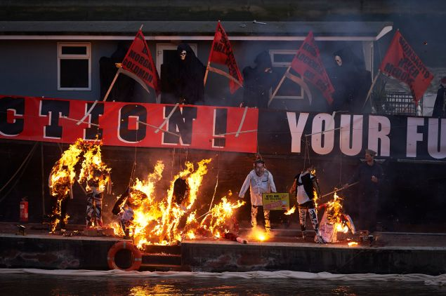 Son of Vivienne Westwood and Sex Pistols creator Malcolm McLaren, Joe Corre, burns his collection of punk memorabilia on a boat moored on the river Thames next to Chelsea Embankment in London on November 26, 2016 in a protest against the Establishments embrace of the 1970s youth movement marking the 40th years since the Sex Pistols released Anarchy in the UK. Corre, son of Sex Pistols manager Malcolm McLaren and the founder of lingerie firm Agent Provocateur, torched the items in protest alongside banners referring to climate change.