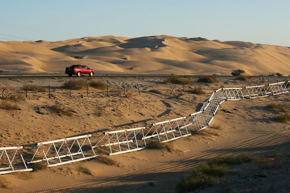 A vehicle-proof barrier lines the south side of Interstate 8 at the Imperial Dunes, a short distance north of the US-Mexico border where no fence divides the two nations, October 8, 2006.