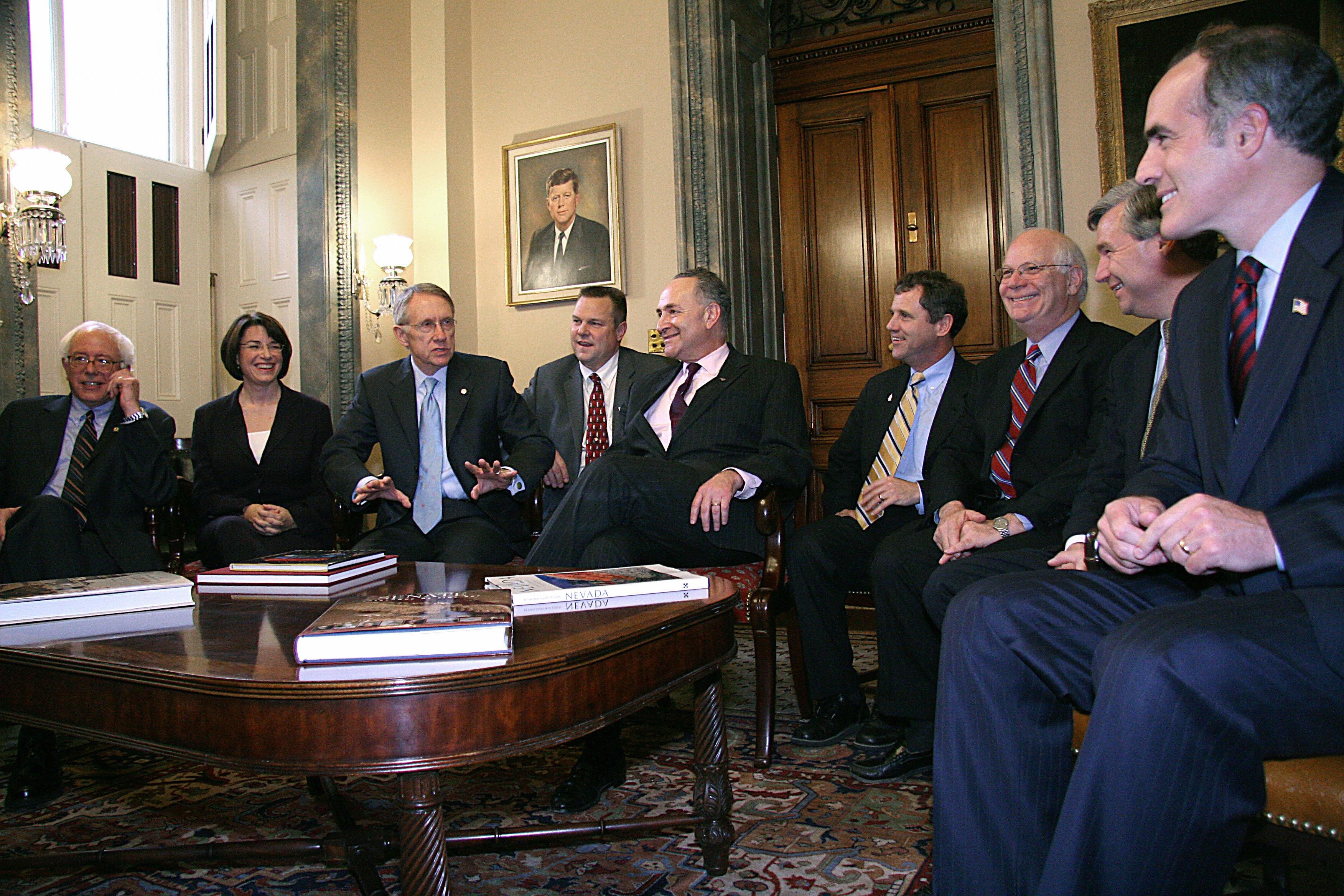 Vermont Sen. Bernie Sanders, far left, and colleagues surround Sen. Charles Schumer, center.