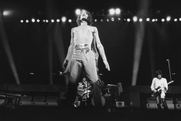 Mick Jagger on stage with the Rolling Stones as they play the last date on their 1976 European tour at the Knebworth Fair festival, 21st August 1976. In the background are (left to right) Ron Wood, Charlie Watts and Keith Richards.