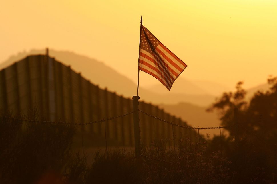 A U.S. flag put up by activists who oppose illegal immigration flies near the US-Mexico border fence in an area where they search for border crossers. US Fish and Wildlife Service wardens and environmentalists warn that an attempt to wall-out illegal immigrants would also harm rare wildlife.