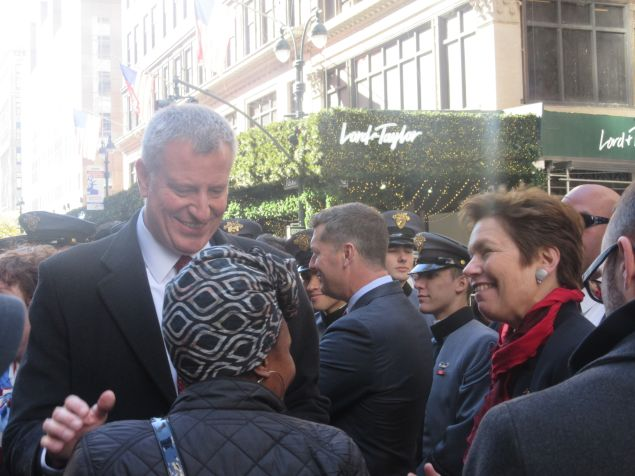 Mayor Bill de Blasio and Veterans' Affairs Commissioner Loree Sutton speak with attendees during Veterans' Day Parade march.