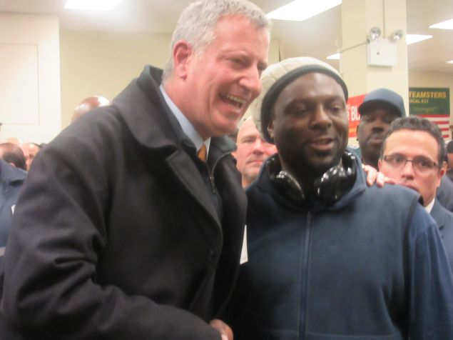 Mayor Bill de Blasio poses with a worker after his speech.