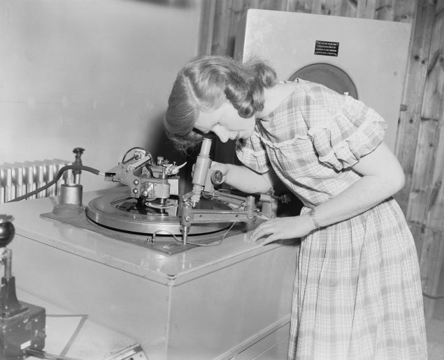 Student Jean Cooke using a microscope to examine the grooves of a record she has just cut, at Wood Norton, a stately home near Evesham, Worcestershire, which is home to the BBC Engineering Training Department, 24th May 1956.