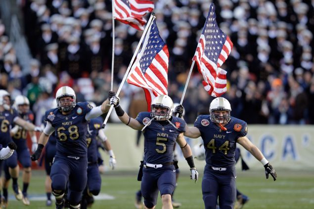 John Dowd #68, Brian Blick #5, and Max Blue #44 of the Navy Midshipmen carry the American flags onto the field before the start of the 112th annual Army-Navy Game of the Navy Midshipmen at FedEx Field on December 10, 2011 in Landover, Maryland.