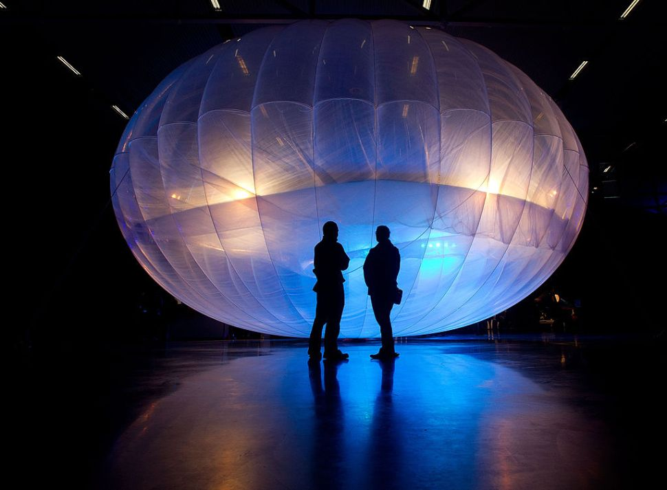 Visitors stand next to a high altitude WiFi internet hub, a Google Project Loon balloon, on display at the Airforce Museum in Christchurch on June 16, 2013. Google revealed top-secret plans on June 15 to send balloons to the edge of space with the lofty aim of bringing Internet to the two-thirds of the global population currently without web access. AFP PHOTO / MARTY MELVILLE (Photo credit should read )
