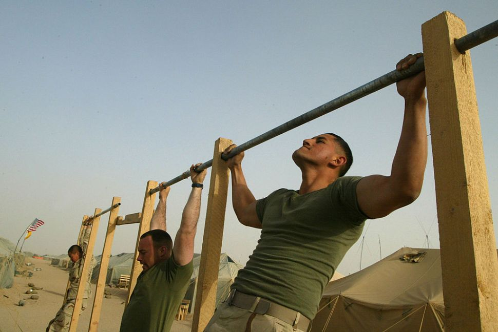 CAMP SHOUP, KUWAIT - MARCH 13: (L-R) U.S. Marines Corporal Norman Doran from Columbus, Ohio and Lance Corporal Diego Carrion from Miami, Florida of Task Force Tarawa do pull-ups March 13, 2003 near the Iraqi border in Kuwait. Thousands of U.S. Marines and soldiers are in the Kuwaiti desert waiting for any orders to attack Iraq.