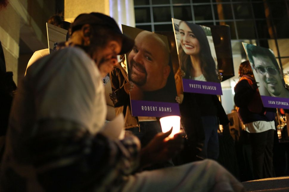 SAN BERNARDINO, CA - DECEMBER 07: Photographs of victims of the terrorist attack on the Inland Regional Center are seen as people hold candles while attending a vigil held at the San Bernardino County Board of Supervisors headquarters to remember those injured and killed during the shooting on December 7, 2015 in San Bernardino, California. FBI and other law enforcement officials continue to investigate the mass shooting that left 14 people dead and another 21 injured on December 2.