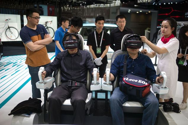 People test a virtual drive of the Kia Autonomous Vehicle at the Beijing Auto Show in Beijing on April 25, 2016. Global carmakers gathered in Beijing on April 25 to show off their wares as competition intensifies and growth slows in the world's biggest auto market, with the key SUV and new energy vehicle sectors the focus of attention. / AFP / FRED DUFOUR (Photo credit should read FRED DUFOUR/AFP/Getty Images)