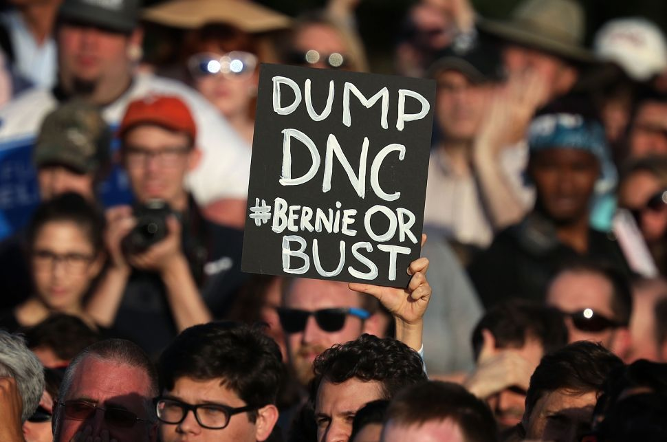 "A supporter holds up a ""DUMP DNC"" sign during a rally of Democratic presidential candidate Sen. Bernie Sanders near the Robert F. Kennedy Memorial Stadium June 9, 2016 in Washington, DC."