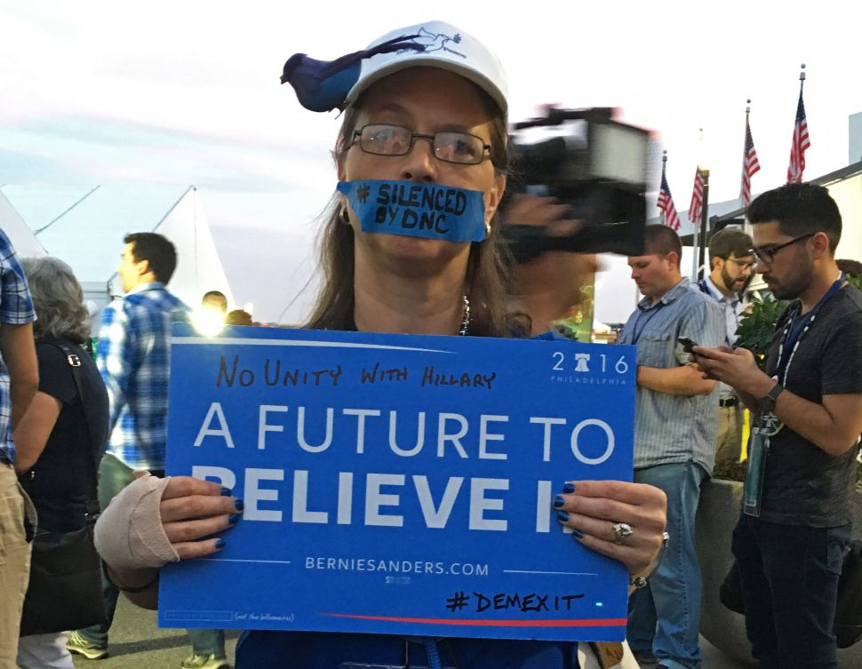 A Bernie Sanders supporter hold up a signs during an improvised protest in front of the media tents on Day 2 of the Democratic National Convention at the Wells Fargo Center in Philadelphia, Pennsylvania, July 26, 2016.