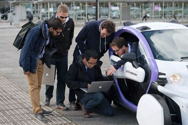Technicans analise data follwong the trial of an autonomous self-driving vehicle in a pedestrianised zone, during a media event in Milton Keynes, north of London, on October 11, 2016. Driverless vehicles carrying passengers took to Britain's streets for the first time on Tuesday in a landmark trial which could pave the way for their introduction across the country. The compact two-seater cars trundled along a pedestrianised zone in Milton Keynes, north of London, in a trial by Transport Systems Catapult (TSC) which plans to roll out 40 vehicles in the city. / AFP / JUSTIN TALLIS (Photo credit should read JUSTIN TALLIS/AFP/Getty Images)