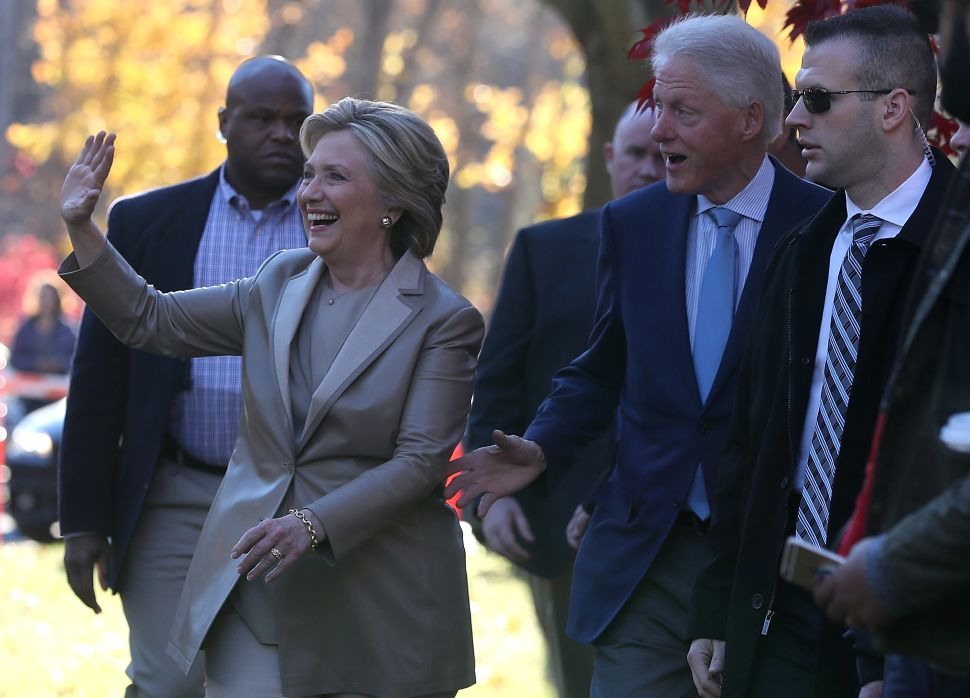 Democratic presidential nominee former Secretary of State Hillary Clinton (L) and her husband former U.S. President Bill Clinton greet supporters after voting at Douglas Grafflin Elementary School on November 8, 2016 in Chappaqua, New York.