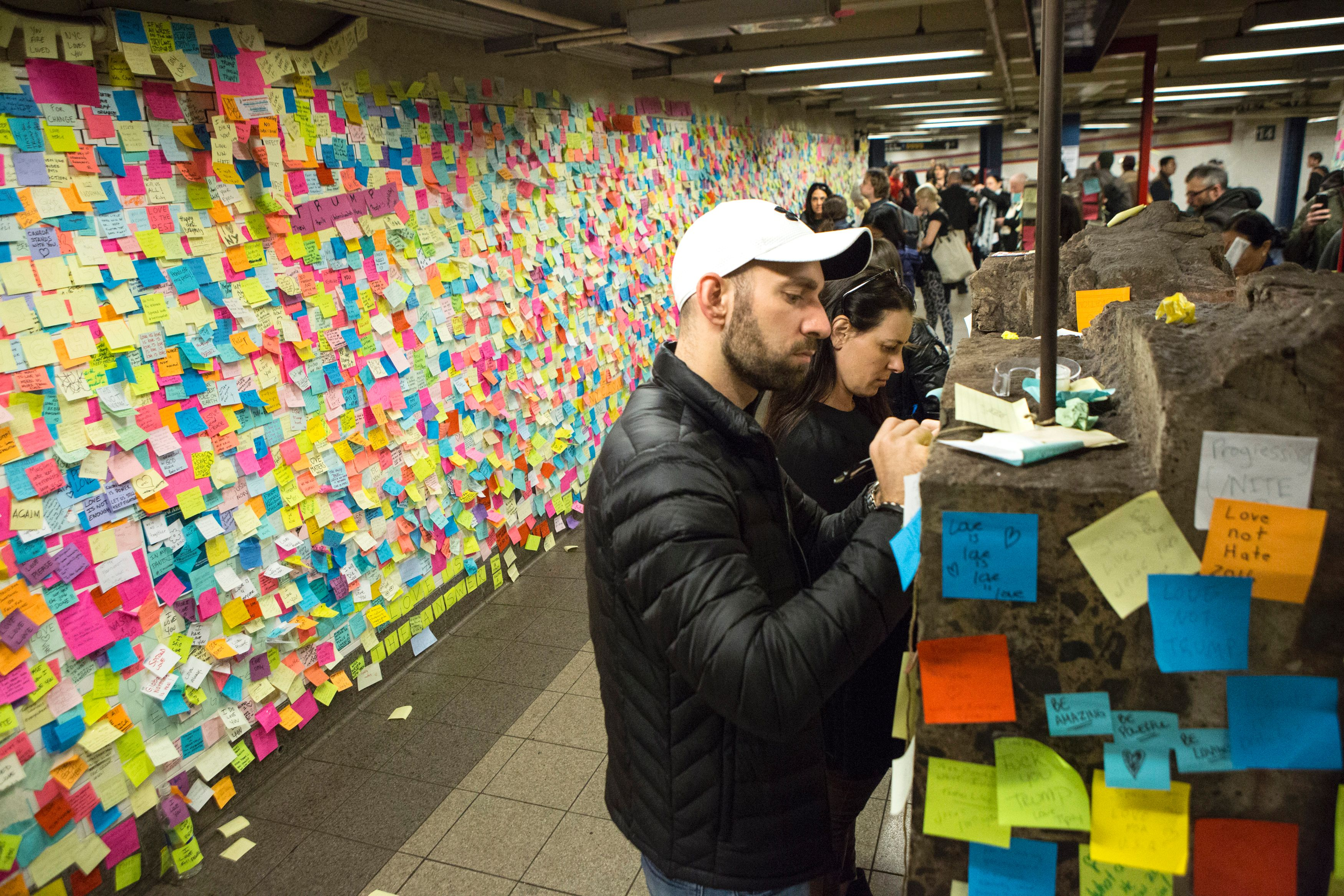 "People stick a Post-It note to participate in the art piece 'Subway Therapy' at the Union Square subway station in New York on November 17, 2016 ""Subway Therapy"" allows people to express their thoughts with the public, and began after the November 8, 2016 US presidential election."