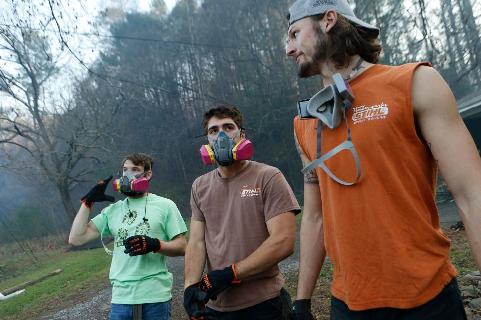 Residents Kirk Wallace, Caleb Graves and Tyler Alden gather to clear debris and put out small fires near surrounding homes as the remains of their neighbors' homes smolder after a wildfire November 29, 2016 in Gatlinburg, Tennessee.