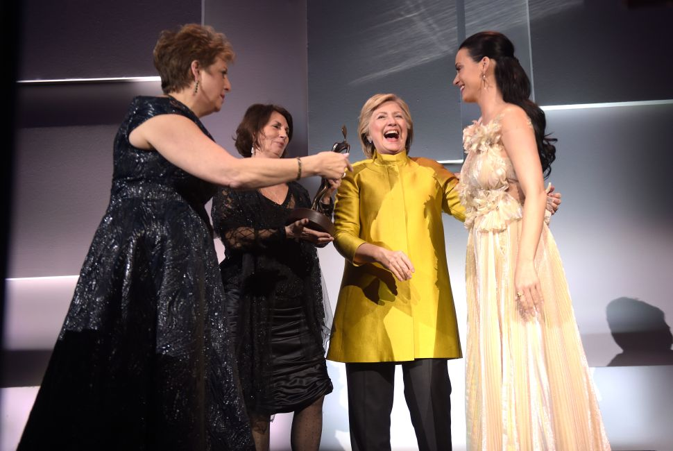 (L-R) Caryl Stern, Pamela Fiori, and Hillary Clinton present the Audrey Hepburn Humanitarian Award to Honoree Katy Perry during the 12th annual UNICEF Snowflake Ball at Cipriani Wall Street on November 29, 2016 in New York City.