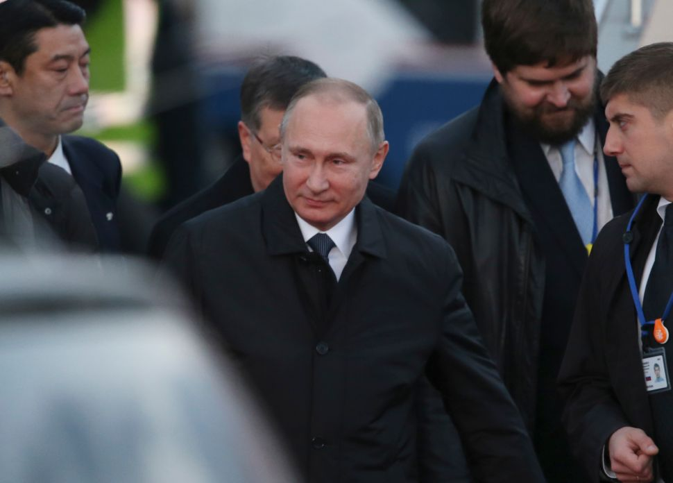 Russian President Vladimir Putin (C) arrives at Yamaguchi Ube Airport in Ube, western Japan on December 15, 2016. Putin arrived in Japan on December 15 for a hot spring summit aimed at reaching a deal over a group of small islands that have prevented the countries from formally ending their World War II hostilities. / AFP / POOL /