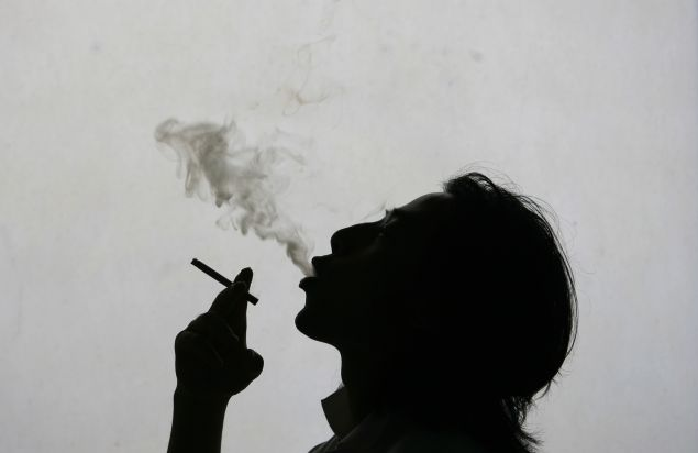 A man exhales smoke while smoking a cigarette on World No Tobacco Day.