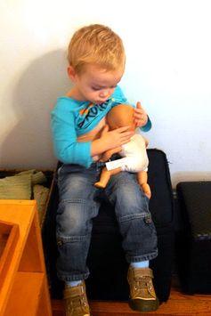 A boy nursing his doll.