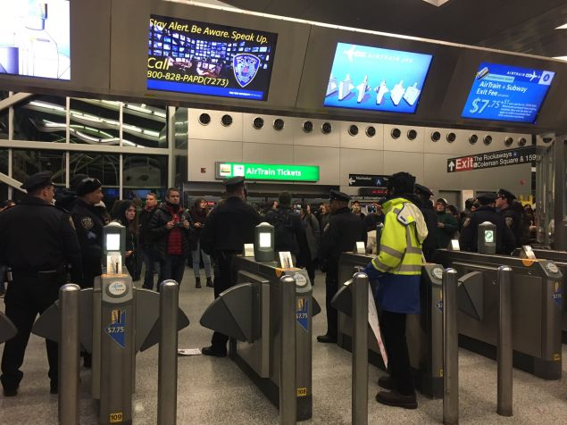 Police officers at Howard Beach tell protestors that only airline passengers and employees can take the AirTrain.