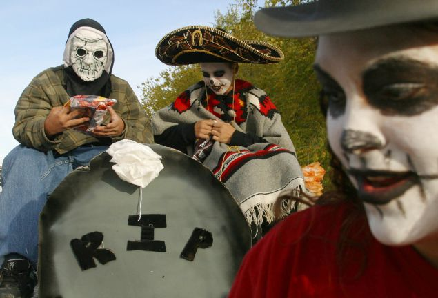 ALBUQUERQUE, NM - NOVEMBER 3: Ray Griego (L), 14, and Emiliano Martinez (C), 13, ride on a float in the 10th annual Day of The Dead Parade November 3, 2002 in Albuquerque, New Mexico. The parade is organized by the Raramuri Center, New Mexico Arts and the New Mexico Endowment For The Arts as a way to bring the community together. (Photo by Phillippe Diederich/Getty Images)