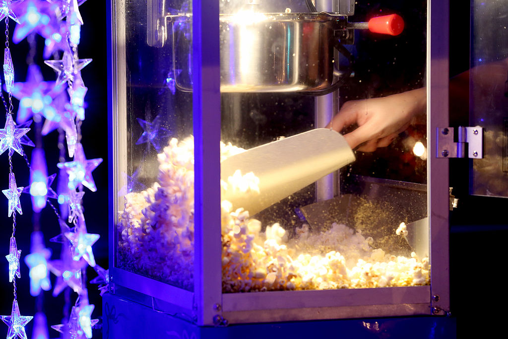 "MIAMI, FL - OCTOBER 11: Popcorn is sold from the concession stand while ""Back to the Future"" plays at The Blue Starlite Mini Urban Drive-In on October 11, 2013 in Miami, Florida. Many traditional drive-in theaters around the United States have closed but the owner of The Blue Starlite held a grand opening for his small outdoor facility, which can accommodate 20 to 24 cars and has seats near the front of the viewing area, with hopes it will become popular in the urban core of Miami. (Photo by Joe Raedle/Getty Images)"