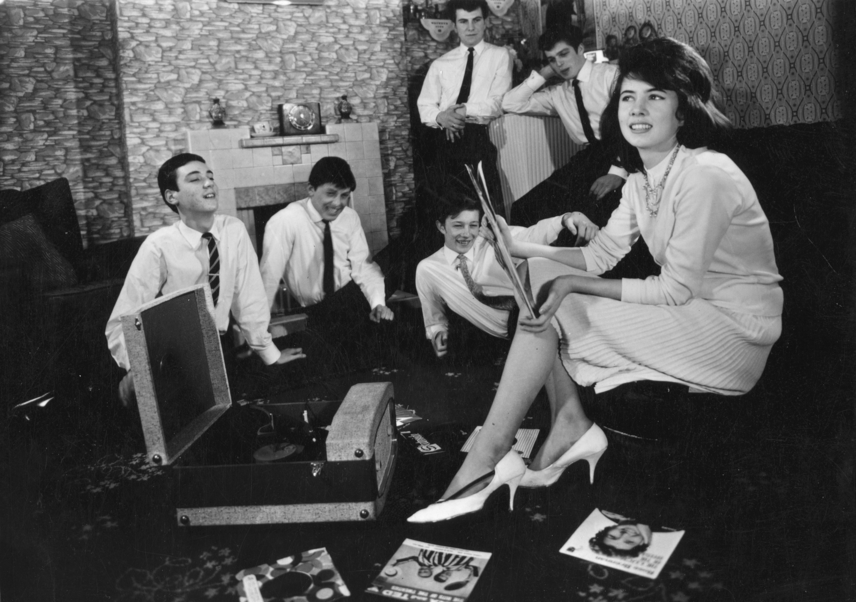 circa 1960: A group of teenagers listening to some records at home.