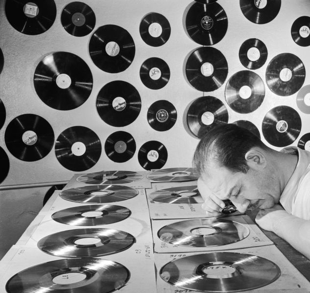 circa 1950: A technician examining the gold-plated master copies of Bibletone religious records.