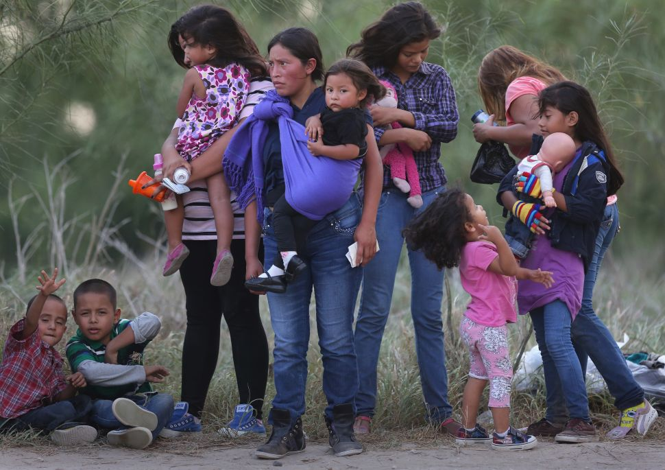 MISSION, TX - JULY 24: Central American immigrants await transportation to a U.S. Border Patrol processing center after crossing the Rio Grande from Mexico into the Texas on July 24, 2014 near Mission, Texas. Tens of thousands of undocumented immigrants, many of them families or unaccompanied minors, have crossed illegally into the United States this year and presented themselves to federal agents, causing a humanitarian crisis on the U.S.-Mexico border. The Rio Grande Sector of the border has the heaviest traffic of illegal crossings of the entire U.S.-Mexico border. (Photo by