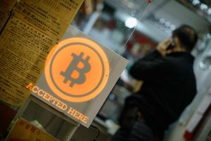 A man talks on a mobile phone in a shop displaying a bitcoin sign during the opening ceremony of the first bitcoin retail shop in Hong Kong on February 28, 2014. Bitcoin was invented in the wake of the global financial crisis by a mysterious computer guru using the pseudonym Satoshi Nakamoto and unlike other currencies, it does not have the backing of a central bank or government. AFP PHOTO / Philippe Lopez (Photo credit should read PHILIPPE LOPEZ/AFP/Getty Images)