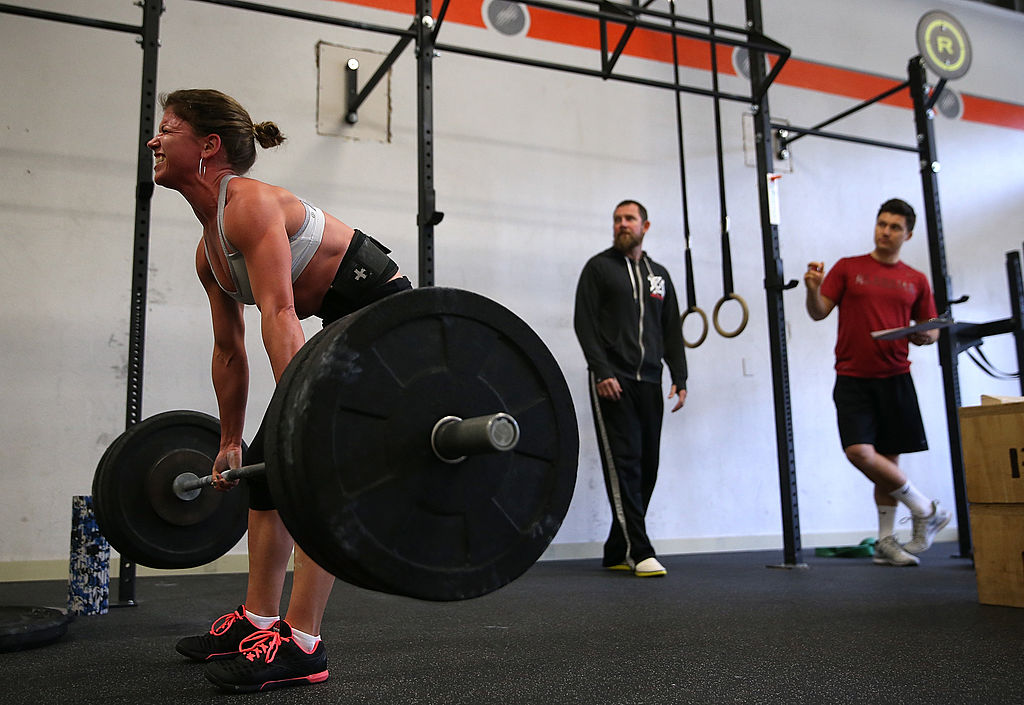 """SAN ANSELMO, CA - MARCH 14: Stephanie St Claire does a deadlift during a CrossFit workout at Ross Valley CrossFit on March 14, 2014 in San Anselmo, California. CrossFit, a high intensity workout regimen that is a constantly varied mix of aerobic exercise, gymnastics and Olympic weight lifting, is one of the fastest growing fitness programs in the world. The grueling cult-like core strength and conditioning program is popular with firefighters, police officers, members of the military and professional athletes. Since its inception in 2000, the number of CrossFit affiliates, or """"boxes"""" has skyrocketed to over 8,500 worldwide with more opening every year. (Photo by"""
