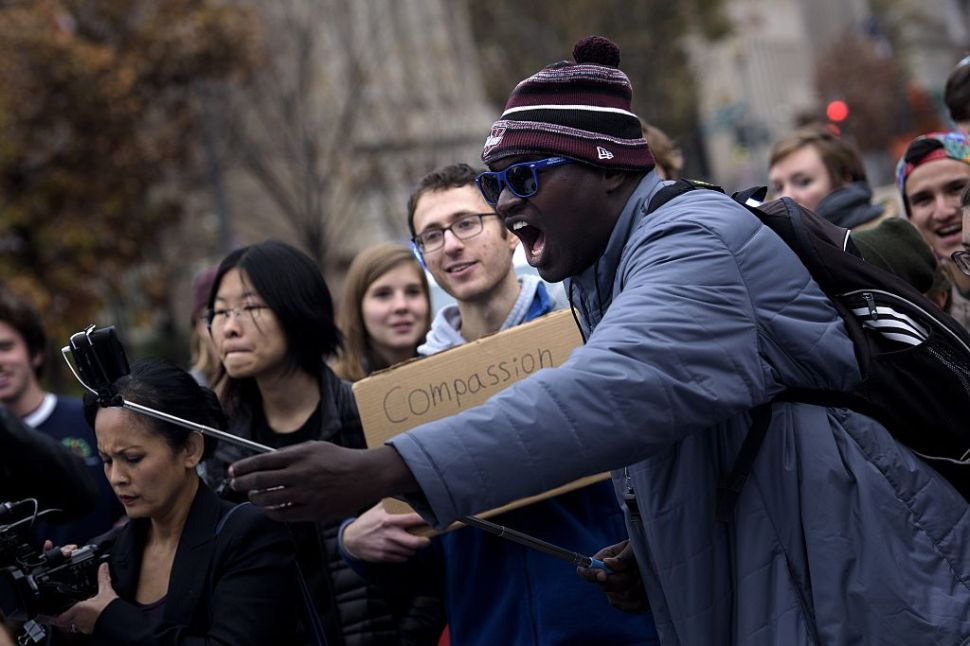A man uses a selfie stick on his smartphone during a protest on H Street near the White House November 9, 2015 in Washington, DC. Activists gathered to protest the mining of fossil fuels, police violence and racism, and immigration issues. AFP PHOTO/BRENDAN SMIALOWSKI (Photo credit should read BRENDAN SMIALOWSKI/AFP/Getty Images)