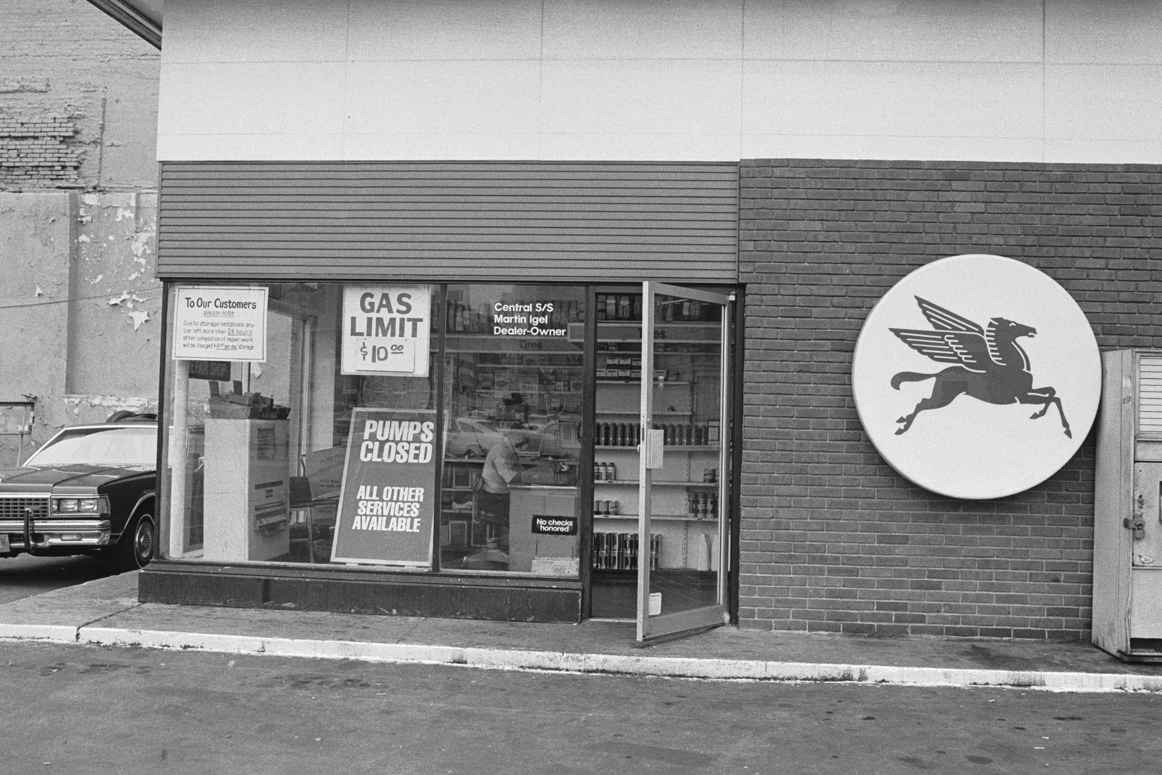 A 'Pumps Closed' sign in the window of a petrol station on 42nd Street and 11th Avenue, New York during a fuel shortage, 19th June 1979. The Mobil Pegasus logo is visible on the right.