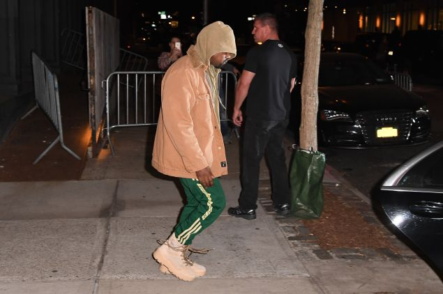 Kanye hides out in a hoodie.