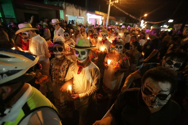"Residents with painted faces and holding candles participate in El Paseo de Las Almas, The Walk of Souls, during a Day of the Dead festival in Merida, Yucatan, Mexico on October 28, 2016. The Day of the Dead in the Mayan area is called ""Hanal Pixan"" in Castilian, meaning food of souls and participants start the parade at the cemetery and walk along the streets with painted faces. / AFP / ALEJANDRO MEDINA (Photo credit should read ALEJANDRO MEDINA/AFP/Getty Images)"