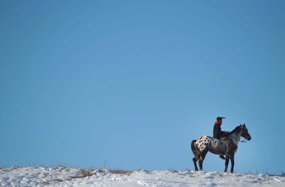 An Native American activist rides along a ridge which overlooks the edge of the Standing Rock Sioux Reservation on December 4, 2016. Activists from around the country gathered at the camp for several months trying to halt the construction of the Dakota Access Pipeline.