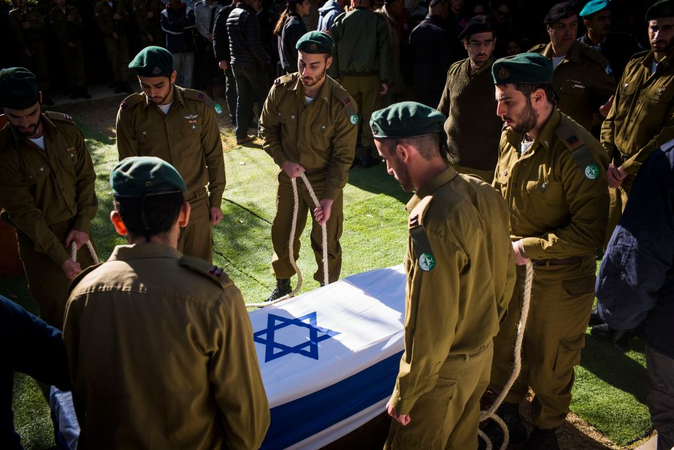 JERUSALEM, ISRAEL - JANUARY 09: The coffin of Shira Hajaj is lowered during her funeral on January 9, 2017 in Jerusalem, Israel. Hajaj was one among the four soldiers killed during the truck attack the previous day.
