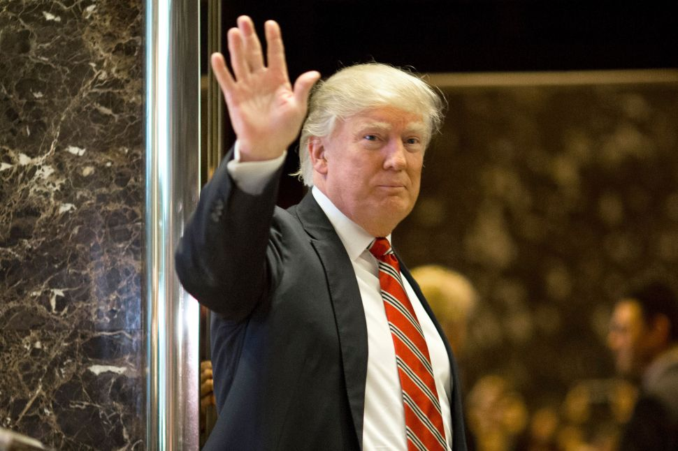 US President-elect Donald Trump waves toward the media after meeting Martin Luther King III at Trump Tower in New York City on January 16, 2017. The eldest son of American civil rights icon Martin Luther King Jr. met with US President-elect Donald Trump on the national holiday observed in remembrance of his late father. / AFP / DOMINICK REUTER