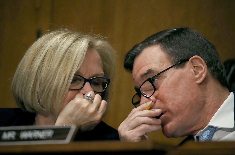 Sen. Claire McCaskill talks with Sen. Mark Warner during the confirmation hearing of Treasury Secretary nominee, Steven Mnuchin, on January 19, 2017.
