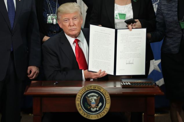 President Donald Trump shows off one of his newly-inked executive orders earlier this week.