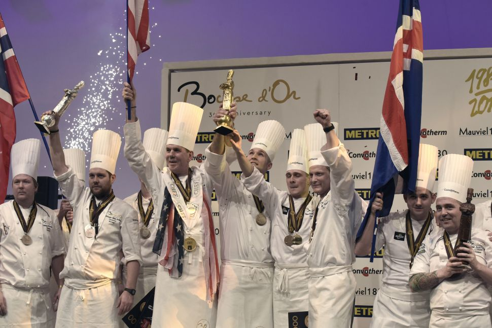 First place winner American Chef Mathew Peters (C), second place Norway's chef Christopher W. Davidsen (L) and third place Iceland's chef Viktor Andresson (R) hold their trophies as they celebrate on the podium after competing in the final event of the Bocuse d'Or International culinary competition, on January 25, 2017 during the catering and food international show (SIRHA), in the French central town of Chassieu, near Lyon. / AFP / JEAN-PHILIPPE KSIAZEK