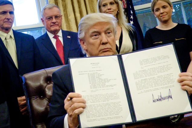 President Donald Trump holds up one of the executive actions that he signed in the Oval Office .