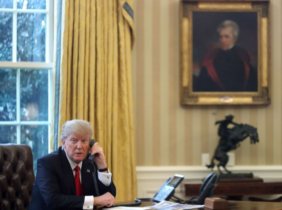 WASHINGTON, DC - JANUARY 29: President Donald Trump is seen through a window speaking on the phone with King of Saudi Arabia, Salman bin Abd al-Aziz Al Saud, in the Oval Office of the White House, January 29, 2017 in Washington, DC. On Sunday, President Trump is making several phone calls with world leaders from the Oval Office.