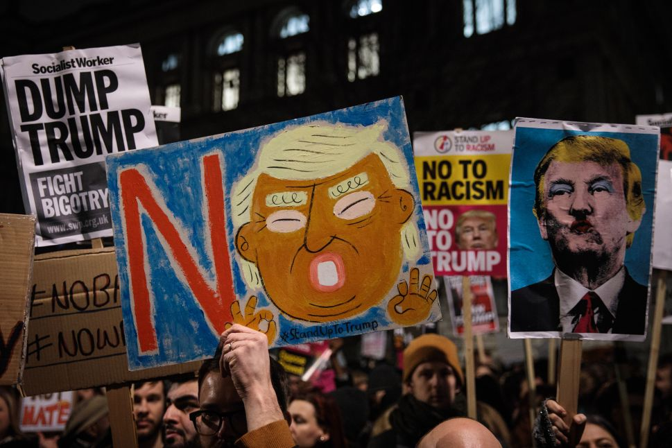 LONDON, ENGLAND - JANUARY 30: Demonstrators hold up placards during a protest outside Downing Street against U.S. President Donald Trump's ban on travel from seven Muslim countries on January 30, 2017 in London, England. President Trump signed an executive order on Friday banning immigration to the USA from seven Muslim countries. This led to protests across America and, today, the UK. A British petition asking for the downgrading of Trump's State visit passed one million signatures this morning.