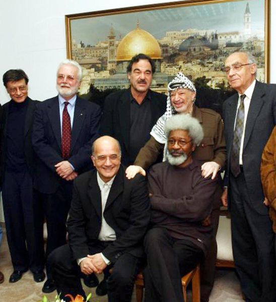 Palestinian leader Yasser Arafat (2ndR)) poses with a group of international intellectuals in March 2002.The group includes from L fo R standing: Palestinian poet Mahmoud Darwish, US writer Russell Banks, US film director Oliver Stone, Portuguese Nobel literature laureate Jose Saramago and seated fellow Nobel literature laureate Nigerian dissident Wole Soyinka (R).